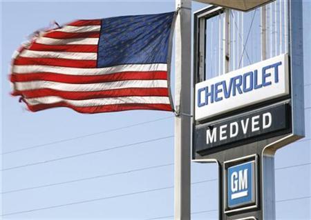 A U.S. flag flies in front of a broken sign at a General Motors dealer in Denver February 26, 2009. REUTERS/Rick Wilking