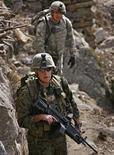 <p>Морской пехотинец (на переднем плане) и пехотинец армии США патрулируют местность у лагеря Combat Outpost Keating в Афганистане 21 января 2009 года. Первая партия невоенных грузов из США, предназначенная для поддержки военной операции НАТО в Афганистане, прошла через территорию России, сообщил сотрудник пресс-службы посольства США в Москве. REUTERS/Bob Strong</p>