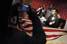 <p>Dei bambini si fanno fotografare accanto alla statua dell'ex presidente Usa Abramo Lincoln al museo di Masame Tussauds a Washington. REUTERS/Jonathan Ernst</p>
