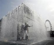 <p>People play in a fountain in front of the renovated Royal Festival Hall in London before the reopening celebrations in this file photo from June 8, 2007. REUTERS/Luke MacGregor</p>