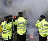 <p>Police cover their ears as firecrackers are set off as part of an official event outside the Chinese embassy during a visit by Chinese Premier Wen Jiabao, in central London in this file photo from February 1, 2009. REUTERS/Andrew Winning</p>