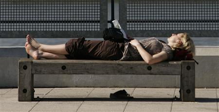 A woman relaxes in the sun by the river Thames in London with the Canary Wharf business district behind May 22, 2007. REUTERS/Luke MacGregor