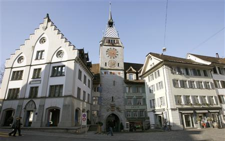 People walk past the 52 metre (171 ft) high Clock Tower, the landmark of the historical part the town of Zug some 35 kilometres (22miles) south of Zurich, February 25, 2009. REUTERS/Arnd Wiegmann