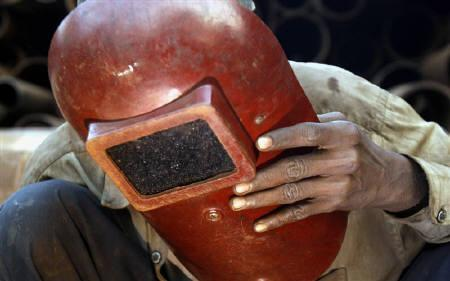 A worker uses a protective shield while using a welding machine at a  workshop in Mumbai in this December 12, 2008 file photo. Factory output fell for the third time in four months in January, supporting the case for further cuts in interest rates as government and central bank action to lift a sagging economy kick in slowly. REUTERS/Arko Datta