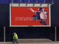 <p>Workmen pass an advertising board for the forthcoming Michael Jackson concerts at the O2 Arena in London, March 13, 2009. REUTERS/Toby Melville</p>