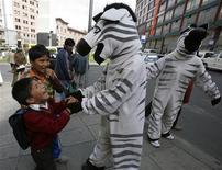 """<p>Residentes vestidos de """"cebras"""" saludan a niños en La Paz, 12 mar 2009. Luis Angel Andrade ha regresado a las calles de La Paz, pero ya no a pedir limosnas ni lustrar zapatos. Junto a otros 70 ex niños bolivianos sin hogar, Andrade se disfraza de cebra y, parado en las intersecciones de La Paz, enseña a los choferes a respetar a los peatones como parte de un programa social de la alcaldía de la ciudad. REUTERS/David Mercado</p>"""