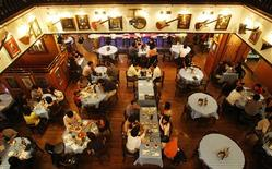 <p>Lunchtime diners sit inside a Hard Rock Cafe restaurant in Singapore March 9, 2009. REUTERS/Vivek Prakash</p>