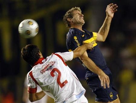 Boca Juniors' Martin Palermo (R) heads the ball under pressure from Argentinos Juniors' Matias Caruzzo during their Argentine First Division soccer match in Buenos Aires March 15, 2009. REUTERS/Marcos Brindicci