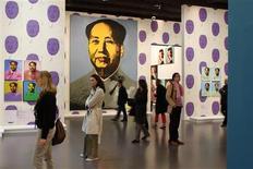 """<p>Visitantes observan retratos de Mao por el artista estadounidense Andy Warhol en la exhibición """"Le grand Monde d'Andy Warhol"""" en el Grand Palais de París, 17 mar 2009. Andy Warhol llega a París en una gran exposición de sus característicos retratos de sociedad, pero sin una famosa imagen de Yves Saint Laurent debido a una disputa sobre si el fallecido modista fue un artista o un mero diseñador. REUTERS/Benoit Tessier</p>"""