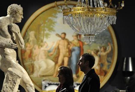 People view a cast of Canova's wrestlers at a display of the fashion designer Gianni Versace's property collection at Sotheby's in central London, March 12, 2009. REUTERS/Toby Melville