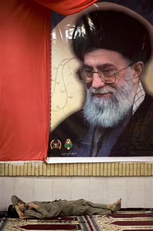 A member of basij militia rests under a portrait of Iran's Supreme Leader Ayatollah Ali Khamenei at an unknown martyrs' shrine at a war memorial site near the Iraqi border 1,257 km (786 miles) southwest of Tehran in Khoozestan province March 18, 2009. REUTERS/Morteza Nikoubazl