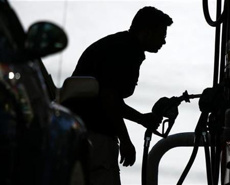 A driver looks at the price of gas at a gas station in Miami's South Beach, April 23, 2008. REUTERS/Carlos Barria