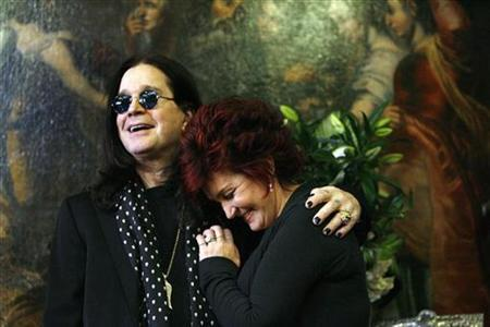Ozzy and Sharon Osbourne smile as they pose in front of some of their belongings to be auctioned in Beverly Hills, California November 26, 2007. REUTERS/Mario Anzuoni