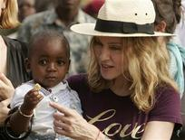 <p>Madonna holds her adopted son, David Banda, at an orphan care centre run by Raising Malawi, a grassroots initiative by Madonna, in Mphendula Village, about 40 km (25 miles) from the capital Lilongwe April 19, 2007. REUTERS/Siphiwe Sibeko</p>