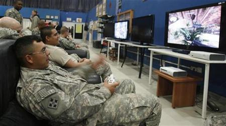 U.S. soldiers play computer games on a television set at the recreational hall of a U.S. military Camp Marez in Mosul, 390 km (240 miles) north of Baghdad January 30, 2009. REUTERS/Erik de Castro