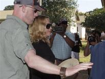 <p>Madonna arrives at the high court escorted by her bodyguards in Lilongwe March 30, 2009. REUTERS/Antony Njuguna</p>