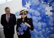 <p>Artist and musician Yoko Ono holds up a piece of her original mural titled PROMISE at the United Nations in New York April 2, 2009. REUTERS/Eric Thayer</p>