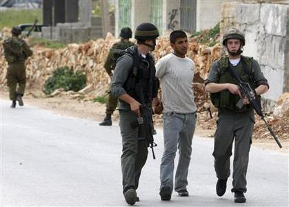 Israeli border police officers detain a Palestinian in the West Bank village of Beit Ummar near Hebron, April 2, 2009. REUTERS/Ammar Awad