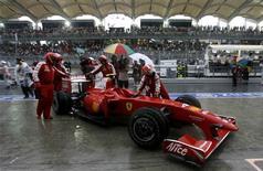 <p>Manutenção da equipe Ferrari com o carro do piloto Kimi Raikkonen no Grande Prêmio da Malásia. 05/04/2009. REUTERS/David Loh</p>
