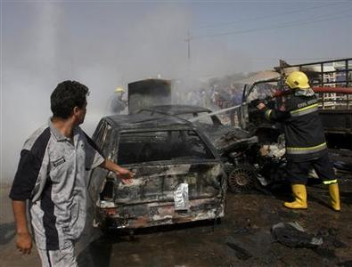 A fireman hoses down burnt vehicles at the site of a bomb attack in Baghdad's Husseiniya district, April 6,2009. REUTERS/Kahtan al-Mesiary