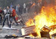 <p>Люди бросают в огонь мебель во время акции протеста в Кишиневе 7 апреля 2009 года. Сторонники оппозиции, не согласные с победой коммунистов на воскресных парламентских выборах в Молдавии, захватили во вторник здание администрации президента и сражаются с полицией в доме парламента. REUTERS/Gleb Garanich</p>