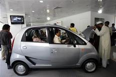 <p>Покупатели рассматривают автомобиль Nano в автосалоне в Бомбее 9 апреля 2009 года. Длинные очереди из потенциальных покупателей автомобиля Nano выстроились в четверг в Бомбее, когда компания Tata Motors объявила о начале сбора заказов на автомобиль стоимостью ниже $2.000. REUTERS/Punit Paranjpe</p>