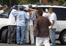 <p>Day laborers swarm a potential employer in a parking lot in Falls Church, Virginia, June 27, 2007. REUTERS/Kevin Lamarque</p>