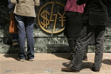 People wait in front of a foreign currency exchange store in Hong Kong April 9, 2009. REUTERS/Tyrone Siu