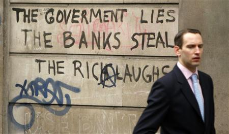A commuter walks past graffiti on the walls of the Bank of England following demonstrations in London in this April 2, 2009 file photo. REUTERS/Stephen Hird/Files