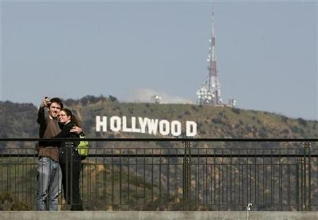Tourist Simon Boulet (L) takes a photo of himself and his girlfriend Estelle Lanoe in front of the Hollywood sign on Mount Lee while visiting Los Angeles from Paris, France as preparations continue for the 81st Academy Awards in Hollywood, California February 18, 2009. EUTERS/Danny Moloshok
