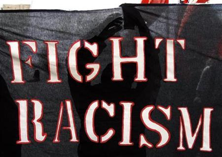 A protester holds a banner during a demonstration against racism in Geneva April 18, 2009. The Durban Review Conference, which will review progress and assess implementation of the Durban Declaration and Programme of Action, will be held at the United Nations European headquarters in Geneva from April 20 to 24, 2009. REUTERS/Denis Balibouse