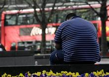 <p>A man sits on a wall in the Canary Wharf financial district of London, April 1, 2009. REUTERS/Simon Newman</p>