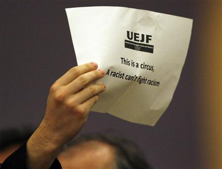 A protestor displays a paper as Iran's President Mahmoud Ahmadinejad addresses the High Level segment of the Durban Review Conference on racism at the United Nations European headquarters in Geneva April 20, 2009. REUTERS/Denis Balibouse