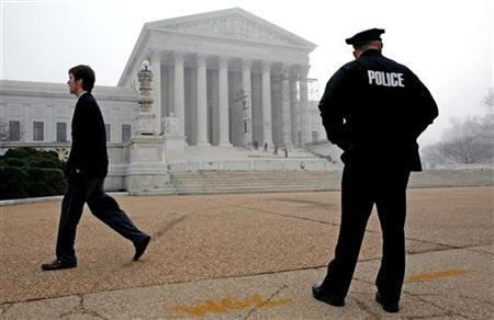 A police officer patrols in front of the U.S. Supreme Court building on Capitol Hill in Washington January 13, 2006. REUTERS/Joshua Roberts