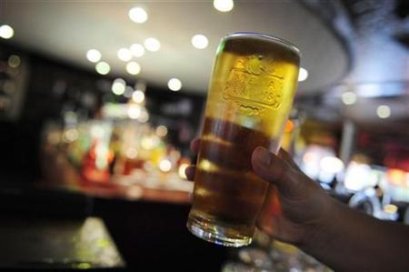 A customer poses for the camera with a pint of beer in a public house in Leeds, northern England October 13, 2008. REUTERS/Nigel Roddis