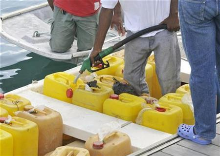 A man fills jerry-cans with petrol at the marina in Marin near Fort de France on the Caribbean island of Martinique February 17, 2009. REUTERS/Isabelle Rouquette