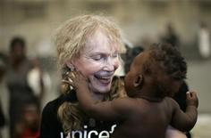 <p>Atriz norte-americana Mia Farrow, embaixadora da Boa-Vontade do Unicef, sorri segurando um bebê haitiano durante sua visita a um abrigo na cidade de Gonaives. 20/09/2008. REUTERS/Eduardo Munoz</p>