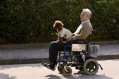 <p>Пожилой мужчина передвигается на кресле-каталке со своей собакой в Шанхае 10 апреля 2009 года. Старение населения угрожает социальной стабильности и экономическому росту Китая, утверждают авторы опубликованного в среду исследования. REUTERS/Aly Song</p>