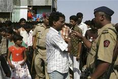 """<p>Un policía habla con Rafiq Qureshi (centro), padre de la niña Rubina Ali (izq) en un barrio de Mumbai, 19 abr 2009. La policía india dijo que no tiene pruebas para sugerir que el padre de una niña protagonista de la oscarizada película """"Slumdog Millionaire"""" intentó vender a su hija. REUTERS/Stringer</p>"""