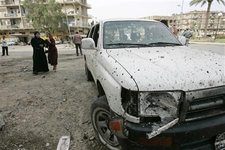 A resident cries near a damaged vehicle at the site of a suicide bomb attack in Baghdad April 23, 2009. REUTERS/Mohammed Ameen