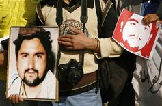 <p>Afghan journalists hold pictures of the late Ajmal Naqshbandi during a protest in front of the Afghan parliament in Kabul April 9, 2007. REUTERS/Goran Tomasevic</p>