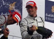 <p>Il pilota di Brawn GP Jenson Button festeggia la vittoria con il pilota della Toyota Jarno Trulli, arrivato terzo, al Grand Prix a Manama. REUTERS/Steve Crisp</p>