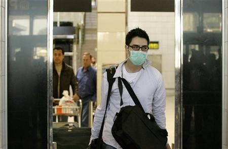 A passenger arriving on a flight from Mexico wears a mask at Barcelona's airport April 27, 2009. REUTERS/Albert Gea