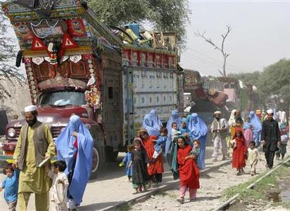 Evacuees from Buner walk next to trucks loaded with their possessions on the outskirts of Peshawar, April 29, 2009. REUTERS/Adil Khan