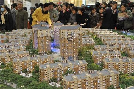 Visitors look at model apartments at a real estate exhibition in Shenyang, Liaoning province March 18, 2009. REUTERS/Sheng Li