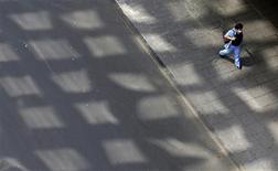 <p>Dans une rue de Mexico, jeudi. Trois cambrioleurs ont profité du port généralisé de masques chirurgicaux bleus, dus à la grippe A(H1N1), pour dissimuler leurs visages et dérober plus discrètement que d'ordinaire des montres au rayon joaillerie d'un grand magasin de la capitale mexicaine. /Photo prise le 30 avril 2009/REUTERS/Daniel Aguilar</p>