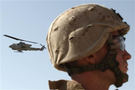 A U.S. Marines Cobra helicopter flies as other Marines patrol a village in the Golestan district of Farah province, April 30, 2009. REUTERS/Goran Tomasevic