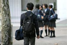 <p>A high school student (L) walks towards a group of female students chatting in front of a school in Tokyo November 9, 2006. REUTERS/Kiyoshi Ota</p>