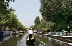 <p>A traditional Venetian gondola passes between narrow boats in the Little Venice area in London July 21, 2006. REUTERS/Toby Melville</p>