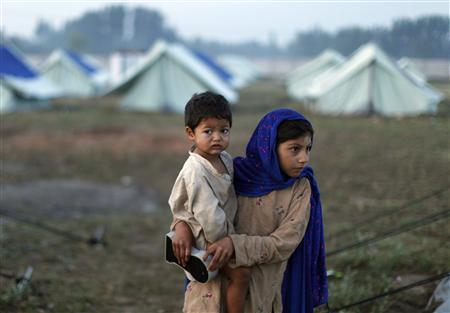 An internally displaced girl, fleeing military operations in Buner, holds her sibling at a UNHCR camp (United Nations High Commission for Refugees) in Mardan, about 100 km north west of Pakistan's capital Islamabad May 6, 2009. REUTERS/Adrees Latif